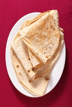 unleavened: Indian unleavened bread chapattis on a plate over a white background.
