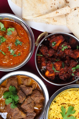 A close-up view of bowls of indian curry - Beef korma and Kasmiri lamb - with chicken fry, yellow rice and a plate of chapattis. Stock Photo - 9232407