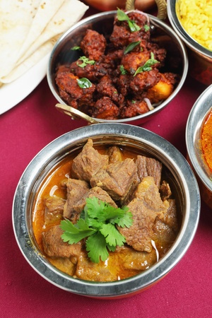 beef curry: A bowl of beef korma curry seen from a high angle, with chicken fry in the bowl behind it