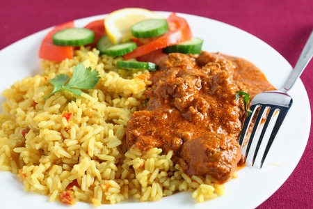 Close-up on a plate of Kasmiri lamb curry with rice and salad on a maroon tablecloth.