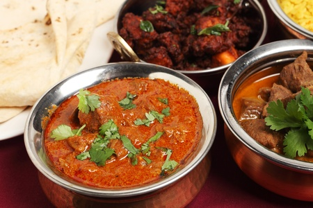 köri: A bowl of Kashmiri lamb curry on a table with lamb korma, chicken fry, chappatis and rice.