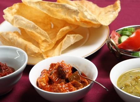 Green mango chutney (front centre), Andhra tomato pickle (left) and lime pickle with a salad and a pile of poppadoms Stock Photo