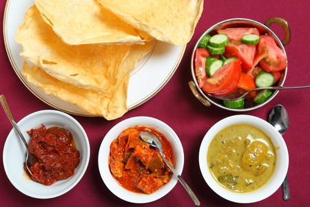 andhra: Indian pappadums with a tomato and cucumber salad and spicy pickles (from left): Andhra tomato  pickle, green mango pickle (or chutney) and white lime pickle