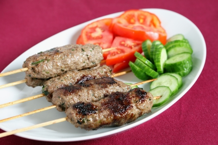 A serving plate of lamb kofta with a salad of tomato and cucumber on a maroon tablecloth
