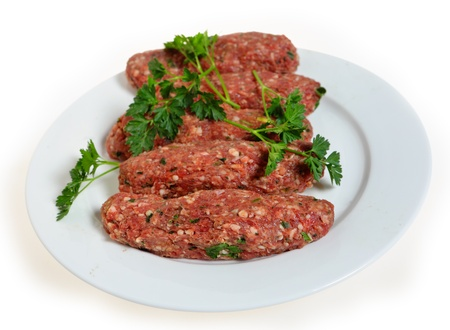 arabian food: Raw lamb kofta, a favourite Arabian grill or barbecue treat, on a white plate.