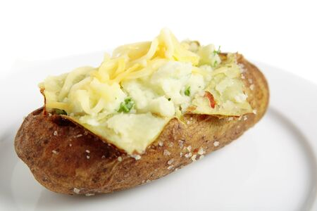 russet potato: A plate with a baked idaho russet potato split open and creamed with butter and fresh parsley, topped with mixed cheddar and mozarella cheeses
