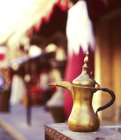 medium shot: A traditional old brass coffee pot in front of a Qatari flag in Souq Waqif, Doha. The coffee pot, or dallah, symbolises welcome in Arab culture. Shot on medium format slide film, selective focus. Stock Photo