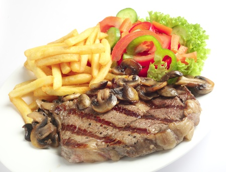 A meal of steak with mushrooms, french-fried potatoes and salad.