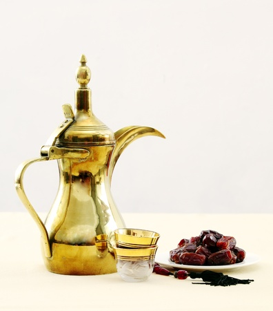 brass plate: A traditional Arabian coffee pot with glass coffee cups a tray of dates and a set of prayer beads. Coffee and dates are often eaten at the end of the fasting period in Ramadan