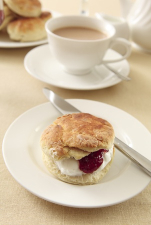 A traditional English cream tea, with scones, strawberry jam and whipped cream, served with tea and milk Stock Photo