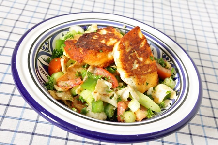 haloumi: A bowl full of fattoush Middle Eastern salad topped with fried haloumi cheese. Fattoush is made with fried or toasted flat bread, chopped tomato, cucumbers, scallions and green peppers, mixed with mint, parsley, oregano, sumac, oilive oil, lemon juice and Stock Photo