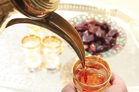 A cup of Arabian coffee being poured with a tray of glasses and dates in the background, traditional fare for breaking the fast during Ramadan.