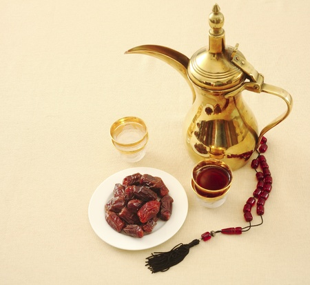 Arab coffee and dates with prayer beads on a tablecloth, with room for text. Coffee and dates are traditionally consumed at fast-breaking during Ramadan