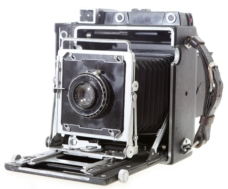 folding camera: A fully working 4x5 American press camera probably c.1958 with a 1920s lens, isolated on white. This was the workhorse for a generation of US pressmen. Stock Photo