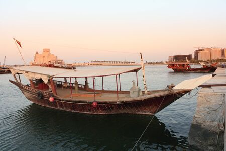 qatar: Two dhows moored beside Dohas Corniche with the Museum of Islamic Art in the background. The wooden ships are still commonly used for fishing as well as for tourist trips. Stock Photo