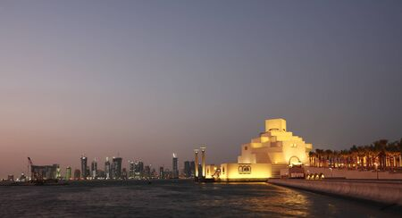 qatar: A view of the Museum of Islamic Art at night, with the Dafna districts high-rise skyline in the background.