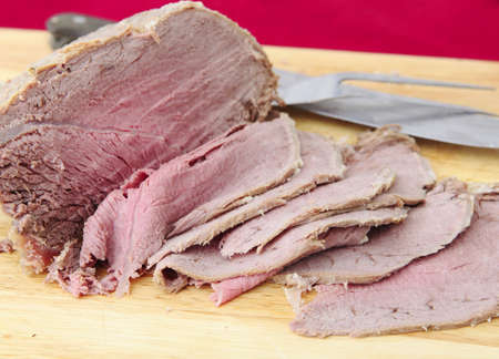 thinly: Cold topside of beef sliced thinly on a chopping board. Stock Photo
