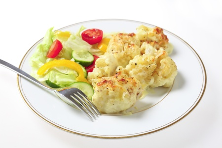english cucumber: A plate of cauliflower cheese served with a fork and a salad of lettuce, cucumber, tomato and capsicum, a traditional English dish.