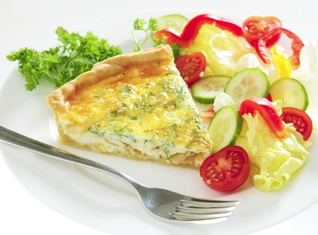 A slice of homemade cheese, onion and parsley quiche with salad and a fork on a plate