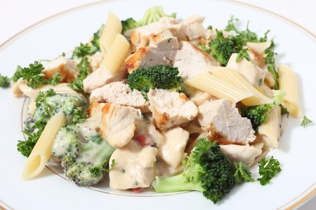 Pieces of grilled chicken served with penne pasta in a broccoli, capsicum and garlic cheese sauce, garnished with parsley. Stock Photo