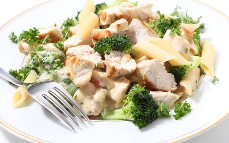 penne: Pieces of grilled chicken served with penne pasta in a broccoli, capsicum and garlic cheese sauce, garnished with parsley. Stock Photo