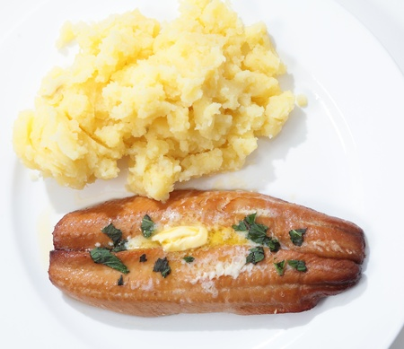 kipper: Top view of a grilled kipper (smoked herring) garnished with butter and herbs on a plate with mashed potato.
