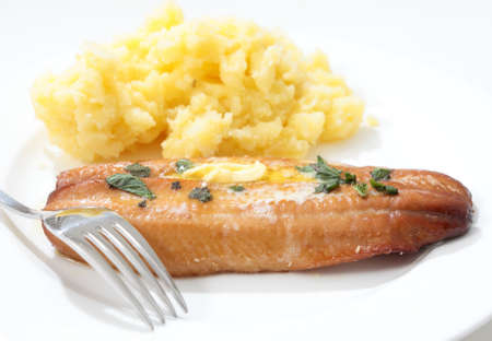 kipper: A grilled kipper garnished with herbs and a dab of butter, served with mashed boiled potatoes Stock Photo