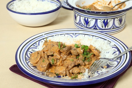 A meal of beef stroganoff with white rice and a fork on a table. Stock Photo