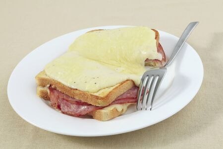 Croque monsieur, a traditional French ham and cheese toastie topped with bechamel sauce and melted cheese on a plate with a fork. photo