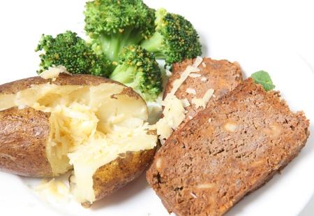albondigas: Una comida de pastel de carne se sirve con papa al horno, queso rallado y el br�coli Foto de archivo