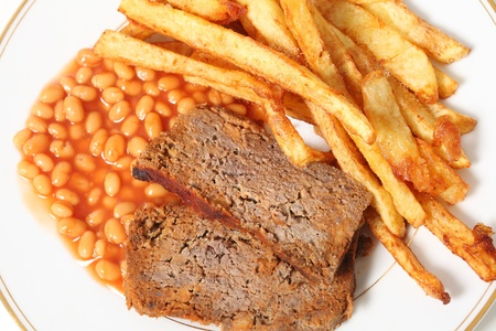 meatloaf: A plate of meatloaf served with baked beans and chips or french fries viewed from above.