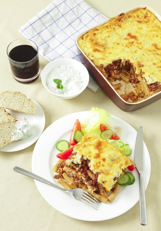tzatziki: Pastitsio Greek taverna type meal with tzatziki, fresh bread and a tumbler of red wine. Stock Photo