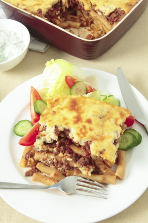 Plate of pastitsio meat and pasta topped with bechamel sauce and cheese, tomato, cucumber and lettuce salad and the serving bowl. Stock Photo