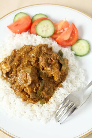 mutton: Lamb rogan josh, with basmati rice and a salad of tomato and cucumber. The lamb, on the bone is in a spicy tomato sauce. Stock Photo