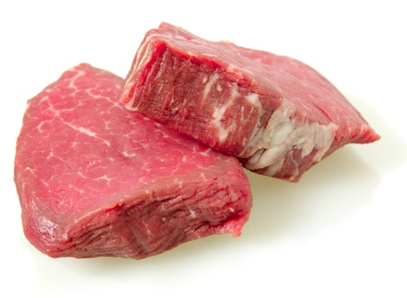 two filet mignon steaks, cut from beef tenderloin, with a light shadow