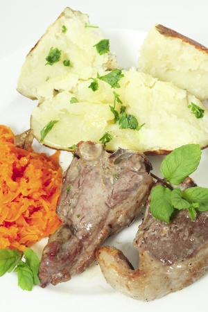 loin chops: a meal of lamb loin chops with a baked potato and grated braised garlic carrots garnished with chopped parsley and sprigs of mint