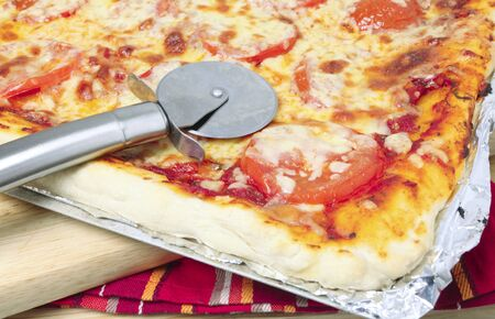 A pizze cutting wheel on a cheese and tomato Sicilian style pizza fresh from the oven photo