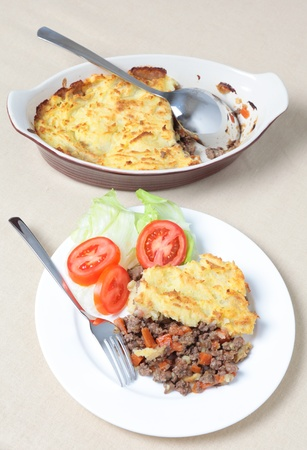 A dinner of shepherds pie or cottage pie and a salad with the serving dish seen from a high angle photo