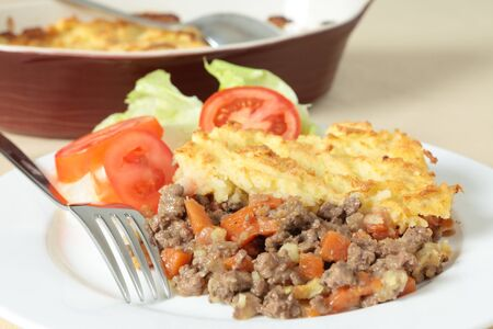 A dinner of shepherds pie or cottage pie and a salad with the serving dish in the background photo