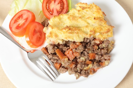 A dinner of shepherds pie or cottage pie and a salad seen from a high angle photo
