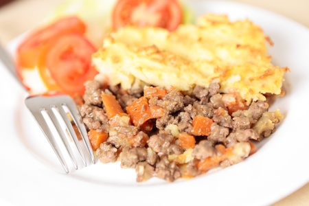 A dinner of shepherds pie or cottage pie and a salad with shallow depth of field photo