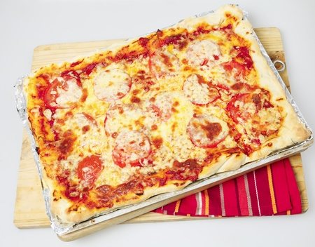 sicilian: An entire Sicilian rectangular pizza with cheese and tomato topping on a baking sheet