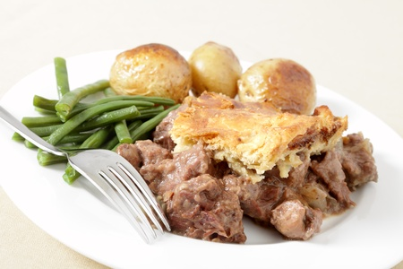 A traditional, home-made steak and kidney pie served with oven roasted potatoes and haricot beans.