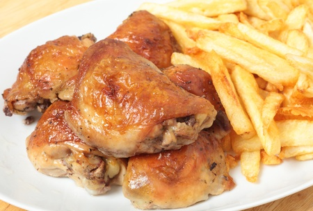 A serving dish piled with roast lemon chicken thighs and French fries, or chips Stock Photo