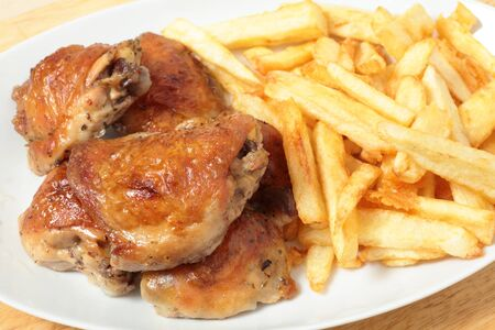 A serving dish piled with roast lemon chicken thighs and French fries, or chips photo