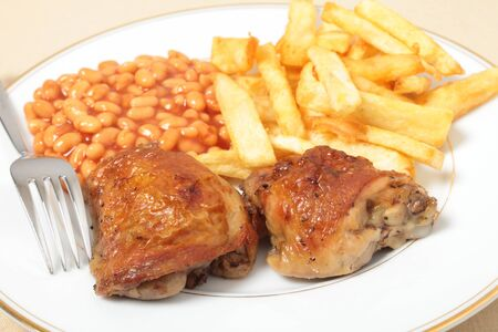 A meal of lemon chicken with french fries and baked beans photo