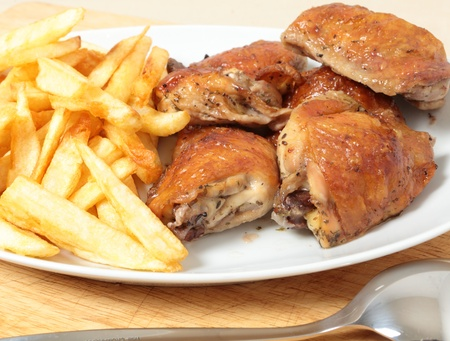 french fries plate: A serving dish piled with roast lemon chicken thighs and French fries, or chips, with a serving spoon