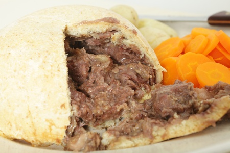 A steak and kidney pudding cut open on a serving platter with carrots and potatoes and the knife in the background photo