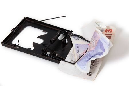 British banknotes caught in the jaws of a rat-trap, symbolising financial dangers and traps, over a white background photo