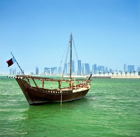 A traditional Arab dhow of the common Shuw'ai type moored in Doha Bay, Qatar, with the city's modern skyline in the background.